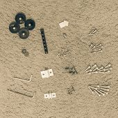 Filtered Tone Furniture Assembly Tools And Screw Nuts On Rough Carpet Background poster