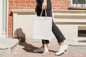 Cropped Photo Of Young Hipster Smiling Girl With White Blank Paper Bag Wearing White T-shirt And Bla poster