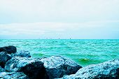 Sailing In The Blue-green Sea. Colored Sails On The Sea Horizon On A Sunny Day. Large Rocks Against  poster