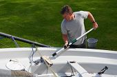 image of dingy  - Middle aged man cleaning his dingy boat in his back yard after a day - JPG