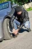 stock photo of revenge  - Man in mask punctures a car tyre - JPG