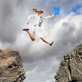picture of gap  - Image of young businesswoman jumping over gap - JPG
