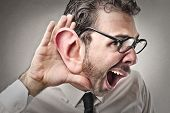 stock photo of deformed  - young businessman tries to listen - JPG