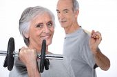 Grey-haired couple lifting weights