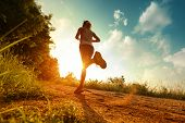 stock photo of cloud forest  - Young lady running on a rural road during sunset - JPG