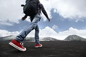 picture of mountain-ash  - Hiker with backpack crossing valley covered with ash towards volcano - JPG