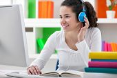 stock photo of schoolgirls  - teen girl doing her homework online and listening to headphones - JPG