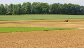 stock photo of horse plowing  - Rural country farmland with men and work horses plowing fields for seasonal planting - JPG