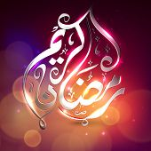 Golden Arabic Islamic calligraphy text Ramadan Kareem or Ramazan Kareem on shiny abstract background