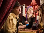 stock photo of seer  - Beautiful fortune teller receiving payment from frowing man - JPG