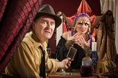 stock photo of seer  - Disgruntled man holding tarot card with nervous fortune teller - JPG