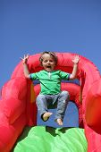 stock photo of inflatable slide  - 3 year old boy jumping down the slide on an inflatable bouncy castle - JPG