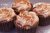 pic of chocolate muffin  - Four delicious chocolate cupcakes with chocolate and sparkles on the top and icing sugar around them - JPG