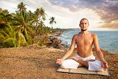 stock photo of breathing exercise  - Yoga meditation in lotus pose by man in white trousers on the cliff near the ocean in Kerala India - JPG