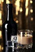stock photo of bailey  - Baileys liqueur in bottle and glass on golden background - JPG