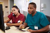 pic of male nurses  - Male And Female Nurse Working At Nurses Station - JPG