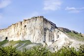 stock photo of crimea  - mountain white frome limestone in Crimea with caves blue sky and green near mountains