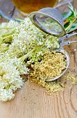 stock photo of meadowsweet  - Metal sieve with dried flowers of meadowsweet a bouquet of fresh flowers of meadowsweet tea in a glass cup on a wooden board - JPG