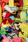 picture of untidiness  - Untidy cluttered wardrobe with colorful clothes and accessories falling out of a shelf - JPG
