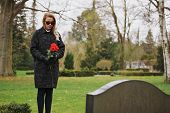 image of grieving  - Young woman standing at graveside of a deceased family member - JPG