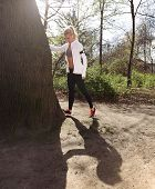 foto of hamstring  - Young woman stretching her hamstrings by a tree before a jog on a forest trail - JPG