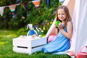 foto of teepee  - Adorable little girl having fun playing outdoors on summer day - JPG