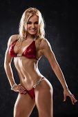 pic of muscle builder  - Smiling athletic woman in red bikini showing muscles on dark background - JPG