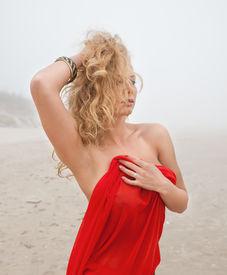 foto of naturist  - Beautiful nude woman in red fabric posing on sea beach in foggy day - JPG