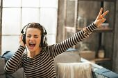 stock photo of cheers  - Cheerful young woman listening music in headphones in loft apartment - JPG