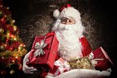 stock photo of beard  - Christmas concept with Santa Claus in costume holding gifts - JPG