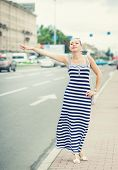 stock photo of hail  - Young beautiful woman dressed striped dress trying to hail a cab in the city - JPG