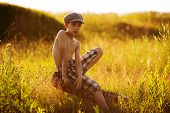 picture of beatitudes  - Teenager in a cap sits on driftwood - JPG