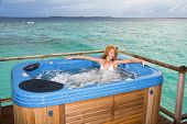 woman in jacuzzi on background of ocean watar villa Maldives poster
