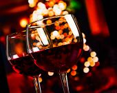 stock photo of alcoholic beverage  - two red wine glass against christmas lights decoration background christmas atmosphere - JPG