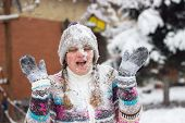 stock photo of snowball-fight  - Portrait of a happy young woman in the middle of a snowball fight on a snowy winter day - JPG