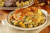 picture of butternut  - A butternut squash and spinach gratin casserole on a holiday table with roast bef in the background - JPG