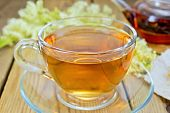 stock photo of meadowsweet  - Meadowsweet tea from a glass cup and teapot - JPG