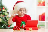 pic of christmas hat  - Happy child girl in christmas hat showing to tablet pc screen - JPG