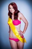 picture of tiara  - Beauty queen wearing a pink bikini and yellow sash with silver tiara on a blue background shot in the studio - JPG