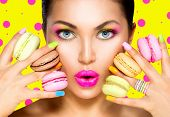 picture of sweet food  - Beauty fashion model girl with colourful makeup and manicure taking colorful macaroons - JPG