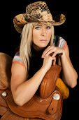 picture of cowgirls  - a cowgirl with a serious expression on her face leaning on her saddle - JPG