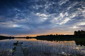 stock photo of pier a lake  - little pier at sunset in a Finnish lake under overcast sky - JPG