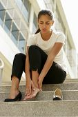 stock photo of foot massage  - Portrait of latina woman walking on high heels and feeling pain massaging feet with hand and sitting on stairs - JPG