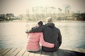 stock photo of pier a lake  - Retro sepia stylized picture of a couple sitting on wooden pier by lake - JPG
