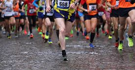 image of competing  - group of runners during marathon while it is raining - JPG
