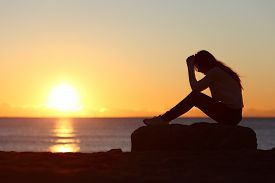 picture of sad  - Sad woman silhouette worried on the beach at sunset with the sun in the background - JPG
