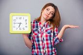 picture of late 20s  - Young casual woman holding clock and shrugging over gray background - JPG