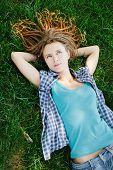 stock photo of dreadlock  - Stylish slim girl with dreadlocks lying on green grass - JPG