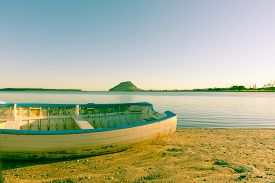 picture of yesteryear  - Old faded effect image clinker dinghy catching morning sun on beach with Mount Maunganui on horizon - JPG