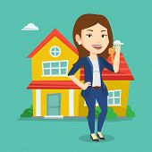 Young female real estate agent holding keys. Smiling real estate agent with keys standing on a backg poster
